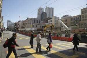 In this Tuesday, July 14, 2015 photo, people cross Stockton Street in San Francisco's Chinatown. A new subway stop is under construction in the background. Rising rent elsewhere in the city has entrepreneurs eyeing Chinatown for offices, entertainment and housing. (AP Photo/Eric Risberg)