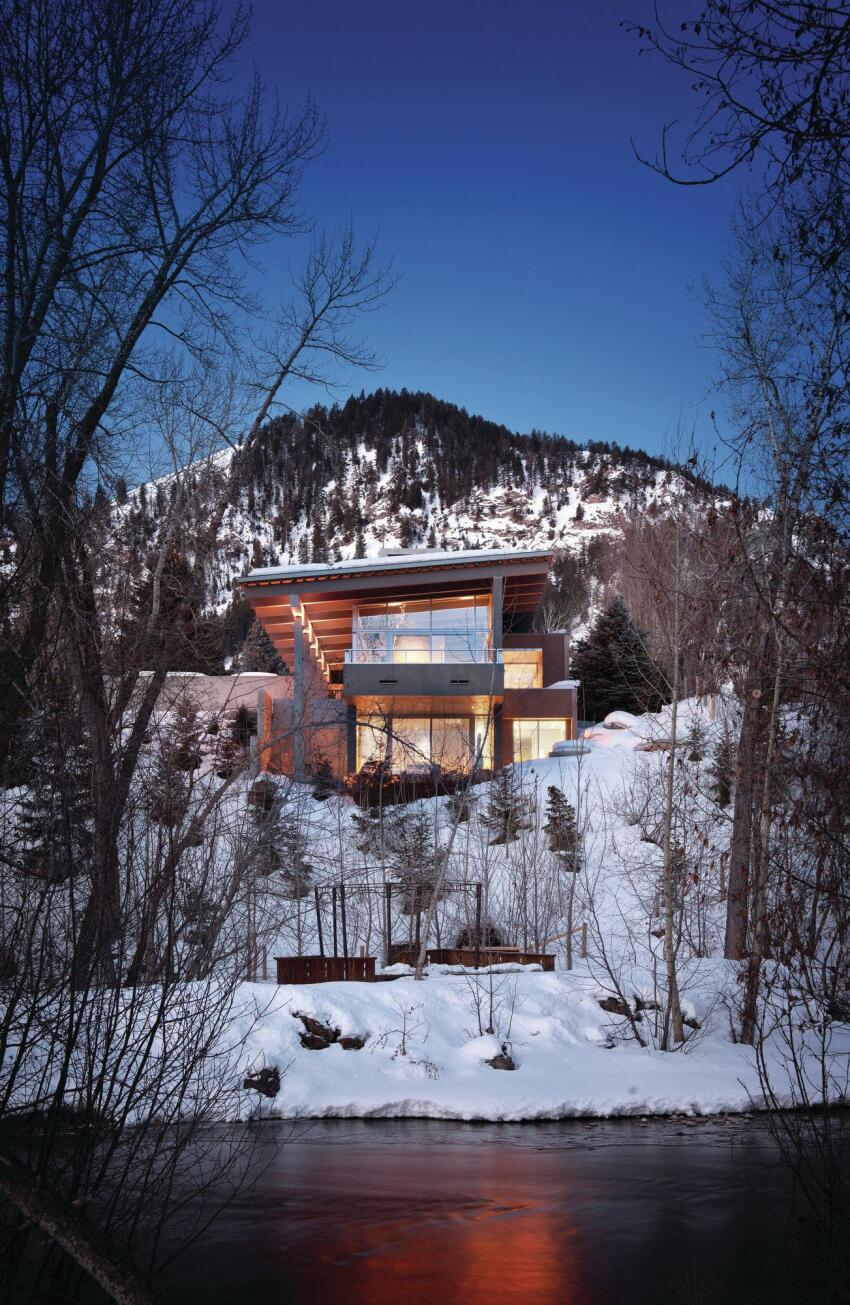 Anchored by an elongated concrete wall to the north, all of the living spaces in the Mountain house are either on or below grade, and are enclosed by glass walls and an exposed-timber shed roof.