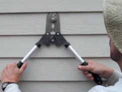 Figure 11. Thin-bladed nail cutters slide under a course of siding to snip the fasteners.
