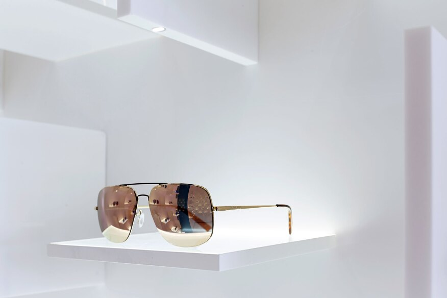 "A detail of the display shelves; each pair of eyeglasses is illuminated via the vertical ""fin"" above."