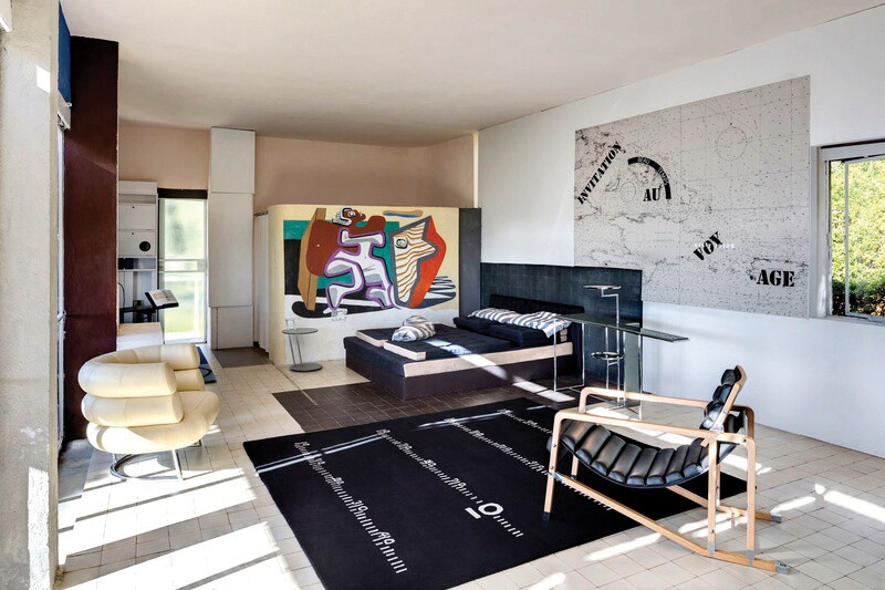 The living room, which features a replica of Gray's Bibendum chair and a Le Corbusier's mural