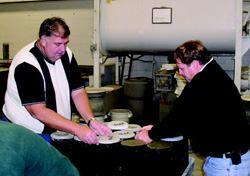 COLD, HARD FACTS: Engineer Brad Barnes (far left) and wall contractor Scott Smith cap test cylinders at the Degussa/Master Builders laboratory in Cleveland. Samples achieved design strength at different times in the freezing test chamber, depending on the mix. Data collected during the test allow contractors to estimate strength gain over time for any of the mixes at any given temperature.