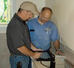 Freyenhagen Construction production manager Dan Wegner shows a detail on his tablet computer to plumber Dave Rabenberg.