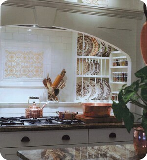 This cooking center has a 36-inch cooktop flanked by shelves and plate racks. Designer Stewart Davis places wood units like this 8 to 10 inches above the countertop to protect the wood from the heat of the cooktop. A ledge along the back of the niche provides additional storage for oils and spices. Davis also incorporated the owners' antique tiles in the backsplash and used crown molding above the niche to create a shelf to display their English pottery collection.