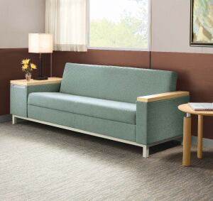 Family members can read or check e-mail from the hospital while or on the LaResta daybed, shown here next to an Orlo table and with optional storage arm.
