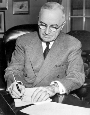 President Harry S. Truman is shown at his desk at the White House. (USIA)