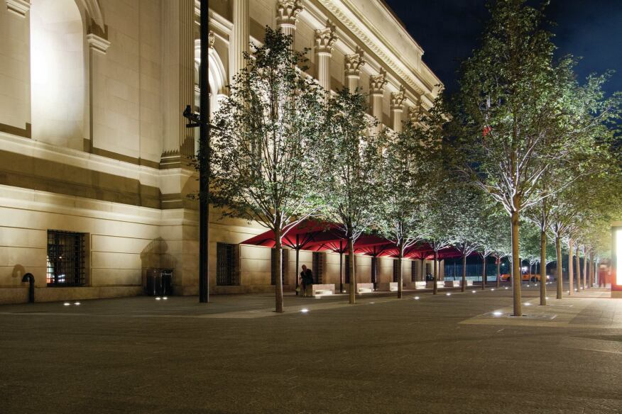 The plaza is transformed at night by the lighting. The allée of London Plane trees are uplit by inground 30W 3500K luminaires. Linear LED fixtures (30W per 8-foot bench) accent the bench seating areas, and 25W LED projectors illuminate the flagpole and the fountains.