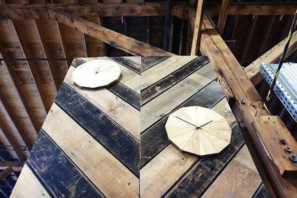 Clocks made from pieces of Ash are mounted for display in the warehouse.