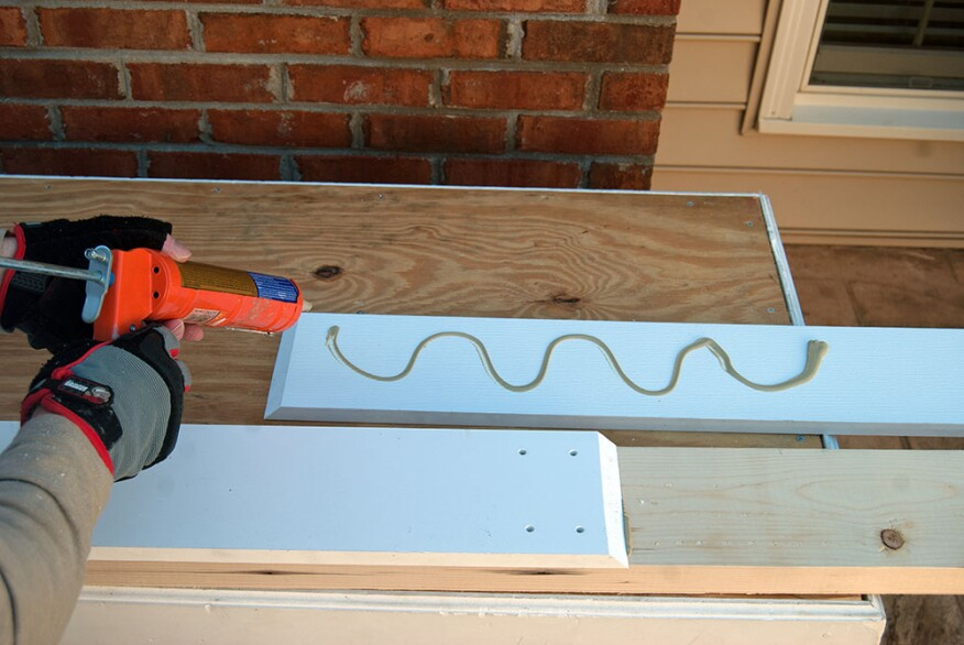 To lock a PVC joint in place, the author begins by gluing the trim to the substrate with construction adhesive.