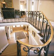Crews stripped the carpet from the winding fir staircase and stained it to create an oxblood look.
