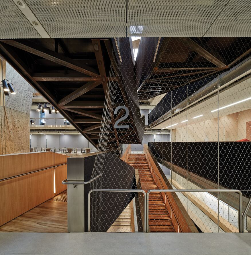 Each level on the stair is noted by a floor number attached to the metal mesh that lines the walls of the atrium.