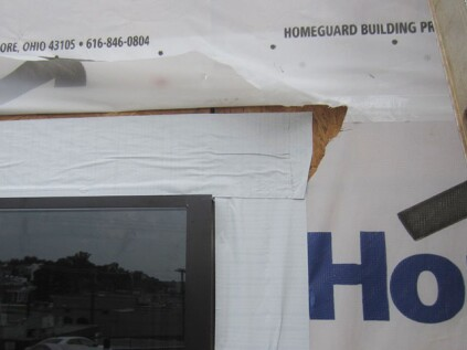 Head flashing. The head flange is covered with a piece of straight peel-and-stick. This flashing must adhere directly to the wall sheathing. Make sure it extends past the outer edges of the window, preferably past the outer edges of the sill flashing tape. The last step is to fold the housewrap back down over the head flashing, and to tape the slits in the housewrap closed.