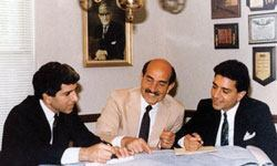 Jirair Hovnanian (center) talks with sons Stephen (left) and Peter (right) in 1985. Overlooking it all: Jirair's father, captured in the framed photo hanging behind them.