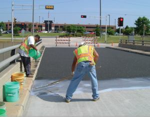 A worker applied the first coat of epoxy with a squeegee at a rate of 30 square feet per gallon.