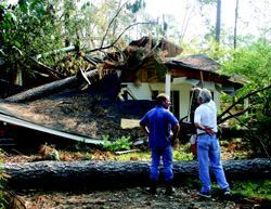"""STARTING OVER: Loranger, La., builder David Reed (opposite page, left) and electrician Don Kennedy (right) inspect Kennedy's ruined house in Mandeville, La., on Sept. 13, along with State Farm insurance adjuster Jesse Curtis (center). Builders and tradesmen are as heavily affected as others in the community by storm damage. At the time of this picture, Kennedy had found an apartment and was working part-time; his destroyed home was 100% covered by insurance, including tree removal, personal belongings, and temporary living quarters. Reed, who rode out the storm at his mother's house on the family farm, was in permitting for a new 20-unit subdivision of 1,500-square-foot homes. """"We know they're going to sell,"""" says Reed."""