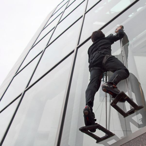 Elliot Hawkes, a mechanical engineering graduate student at Stanford University, scales the exterior of a glass wall using adhesive grips.