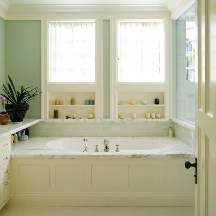 For privacy, architect Aleck Wilson placed the sills of the windows above waist height. He located the window heads at the ceiling trim and filled the spaces below them with shelf niches.
