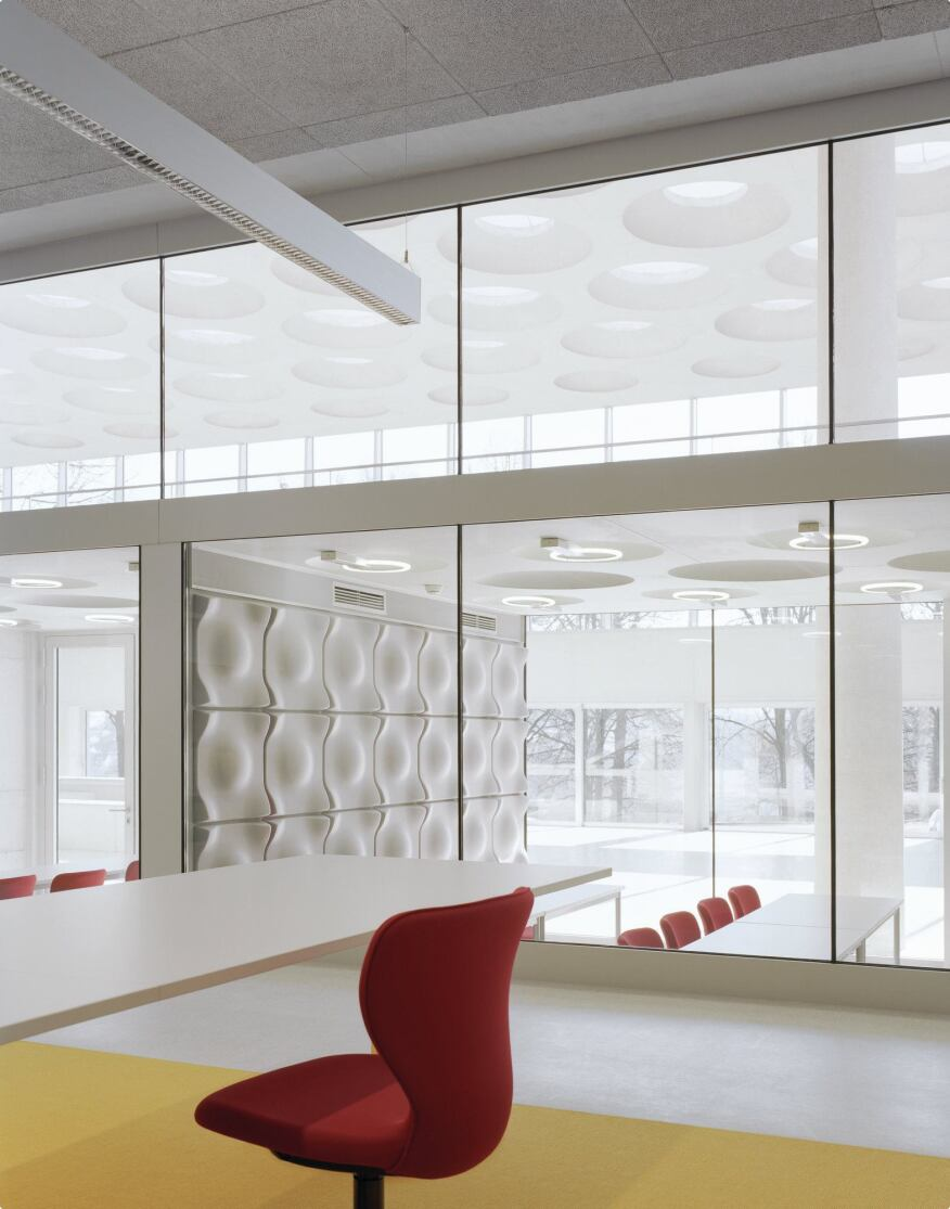 Library reading tables overlook the multipurpose rooms on the ground floor and the bridge leading to the café on the second floor. The glazing is from Balardo. Here, and in other study spaces, ceiling panels from Heraklith further dampen sound.