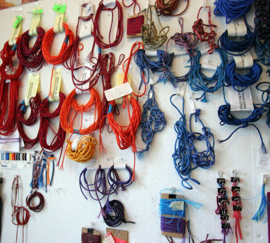 Different types of threads, strings, and fibers on a material wall in Echelman's studio in Brookline, Mass.