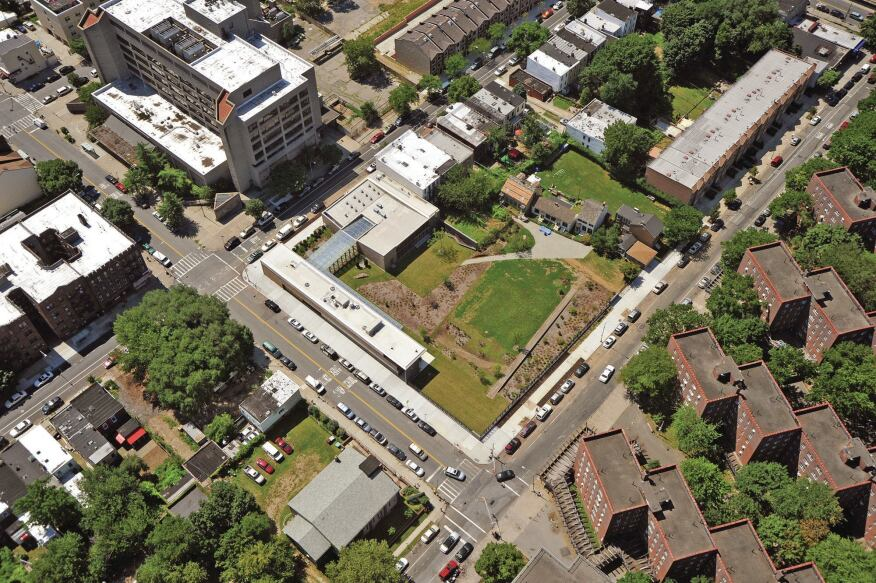 An aerial view shows how the new center frames the four historic houses (at upper right) on the 1.5-acre site. Where not bounded by buildings, the perimeter is enclosed by a cast-iron fence from Allen Architectural Metals.