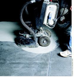 The floor polishing process begins by grinding and smoothing a concrete floor with diamond abrasive discs fitted to a floor grinder.