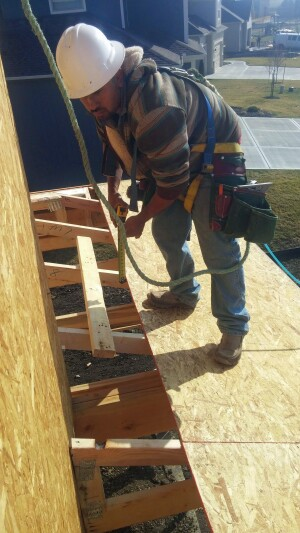 On a Summit Custom Homes jobsite, a framing carpenter wears a safety harness secured to a point above him while working on the roof. He is wearing a hardhat and shoes that have good traction for the slope of the