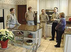 "Scott Watson (second from right) on the ""set"" of ""Rescue My Kitchen,"" with crew and homeowner Linda Grelle (right)."