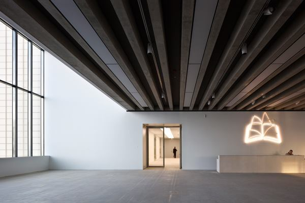 Turner Contemporary Gallery, by David Chipperfield Architects. The foyer is lit by two-story windows and has a low ceiling, which shades entrants from the noon sun and provides enough shadow for the line drawing of a book by Michael Craig Martin to glow faintly in pink neon.