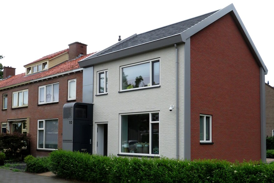 A side-by-side illustration of an existing building (left) and the retrofit (right), as part of the Energiesprong program in the Netherlands. The renovated house features a new insulated façade, insulated roof, and an exterior mechanical room.