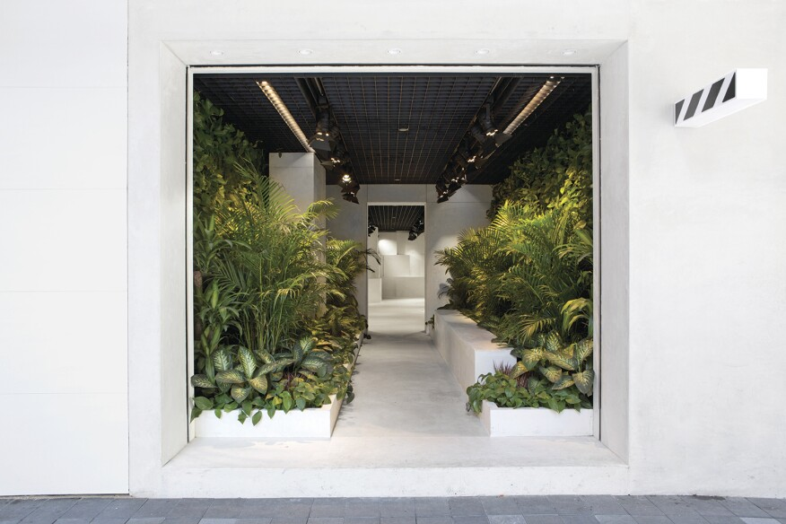 The Off-White boutique in Hong Kong mimics the city's diametric nature with a lush, jungle-like garden in the front, and a layered accretion of concrete cubes in back.