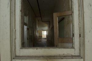 Door frames leading down empty hallway of abandoned school.