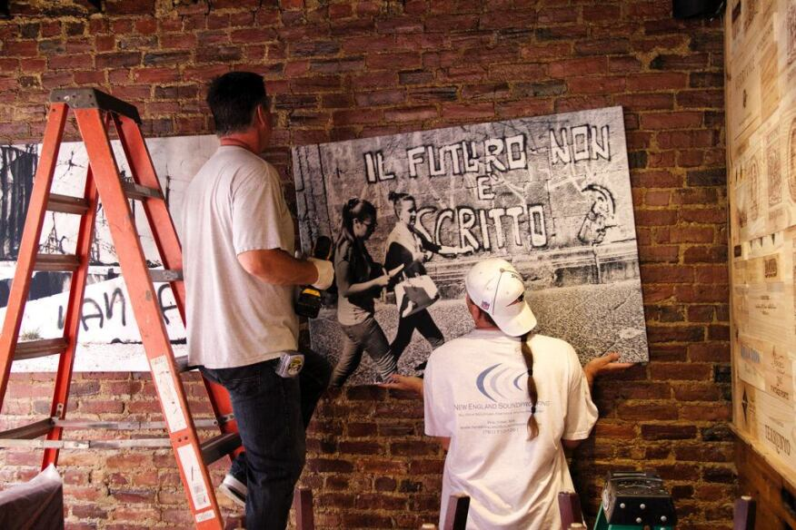 the crew hangs panels on the echoing brick walls of a North End restaurant, where the product will provide visual interest as it quiets the space.