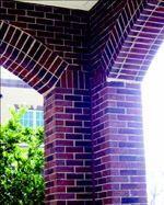 The thin brick is carried to the back side of the tilt-up panels to give the appearance of solid brick piers and arches.