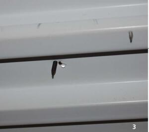 (3) Moisture is dripping out of the errant screw hole. Repetitive wetting will result in roof-deck corrosion and, when located at screw fasteners, loss of wind-uplift resistance.
