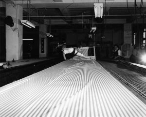 Garment worker laying out fabric to prepare for cutting
