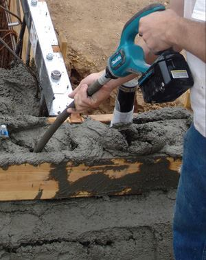 The vibrator is carefully placed so that it does not touch any of the rebar in the concrete.