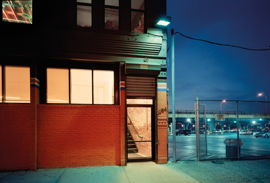 "West 126th Street, New York""I am intrigued by the variety of colors of light falling on the building and the adjacent parking lot. The abrupt combination of warm and cool light is a characteristic I frequently see as night falls."" -- Lynn Saville"