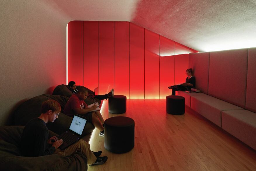 In the Student Lounge, light behind the banquette creates an intimate lighting effect along with a red (the University's signature color) backlit glass wall.