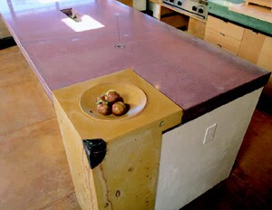 The large island countertop has a fruit bowl and an art piece built into it.