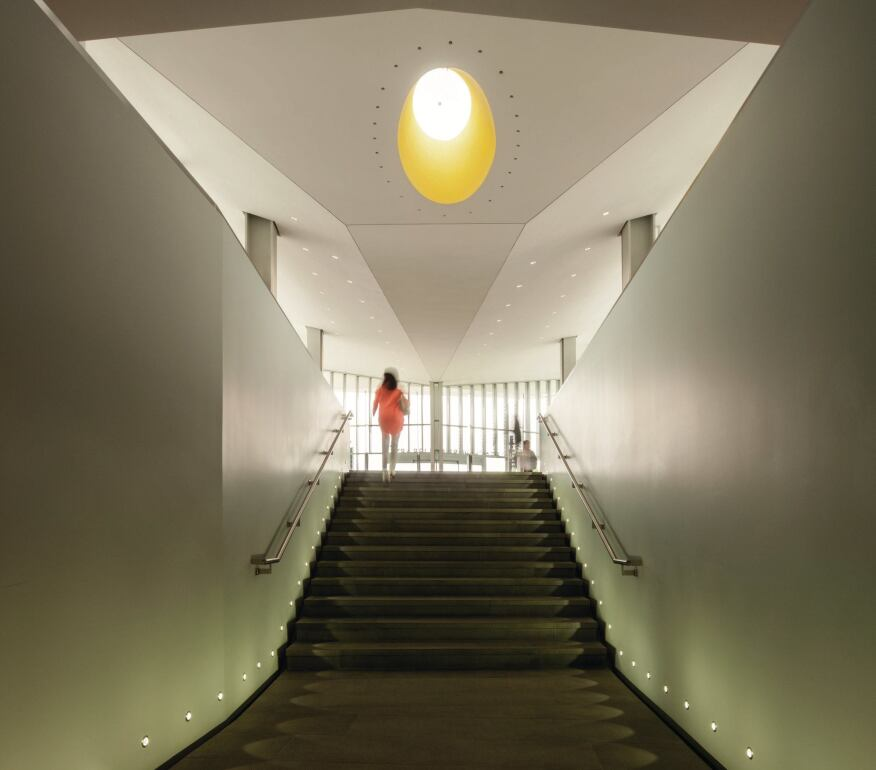 A stairwell in the library addition is capped by a yellow-painted oculus.