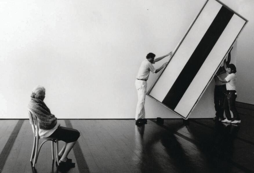 Dominique de Menil oversees workers as they hang a painting by Barnett Newman in the Menil Collection museum.