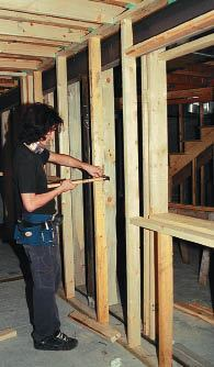 Parallel 2x4 partition walls provide acoustic separation between rooms. To reduce sound transmission to the living space above, the author dropped separate 2x10 ceiling joists below the plane of the I-joist floor system.