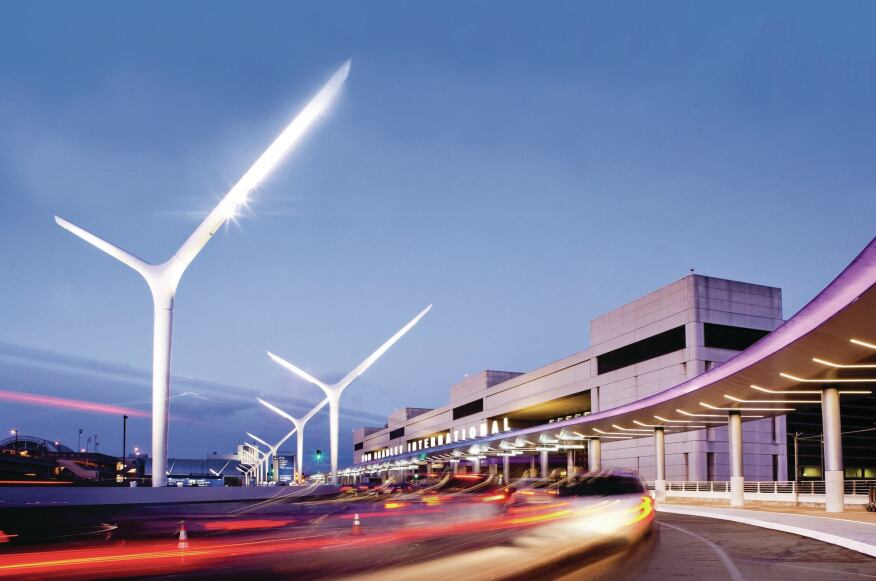 Improvements to the curbside environment at LAX's Tom Bradley International Terminal (TBIT) include sculptural light poles, under-canopy lighting, and a color-changing light ribbon along the canopy edge.