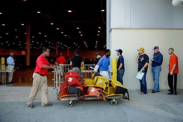 Workers help load cars and trucks with seats sold at the firesale.