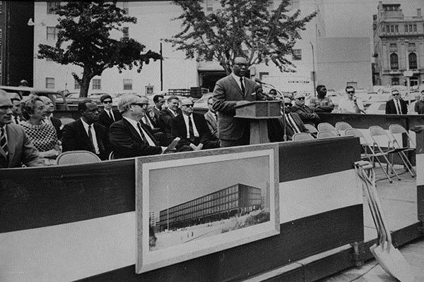 Mayor Walter Washington speaks at the 1968 groundbreaking ceremonies of the MLK Library, pictured in the architect's drawing in front.