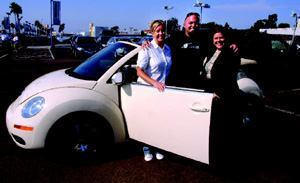 CAR CRAZY: Katherine Elder (left) is one of three lucky winners of a VW Beetle convertible. The  cars were raffled off by The Corky McMillin Cos. this past summer  to generate sales traffic in six of the builder's San Diego communities.