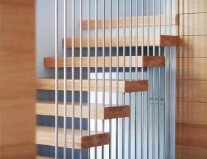The stainless steel rods are joined by threaded couplings hidden within the thickness of the wood.