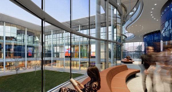 Each area between the elliptical classrooms and curved glazing features lively gatherings on banana-shaped furnishings.