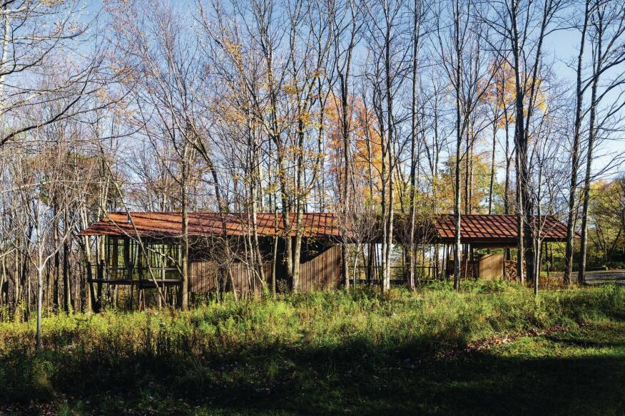 Seen from the northwest, the guest house and artist studio appears to float in the landscape; the structure is supported by steel columns on piers to accommodate the steeply sloping grade.