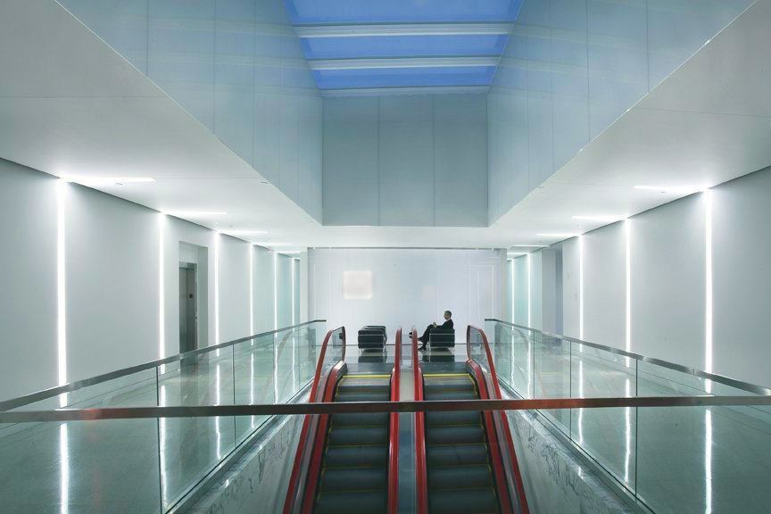 A pair of Schindler escalators, in signature red, face a white accent wall and connect the main and upper levels of the company's headquarters.